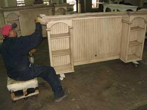 An Eagle Inds. worker sands a hutch for an entertainment console in the American Premiere line, which has high-end design elements and is at the top of Eagle's price range.