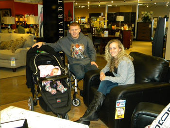 Wounded Army veteran Brett Bondurant, center, with his wife, London, and daughter, Jacee, at Morris Home Furnishings in Cincinnati. Morris and community donors are helping to furnish the family's home.