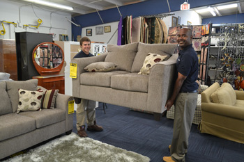 Furniture For Change sales associates Austin Payne, left, and Corey Booker, at work in the store.