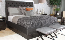 This upholstered panel bed is part of Lexington Home Brands Carrera collection. It features a charcoal textural fabric in a diamond-tufted pattern that is bordered with nailhead trim.