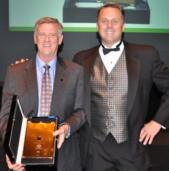 AMP rep award winner David McElveen, left, receives his prize of a gold iPad from AMP CEO Patrick Henley.