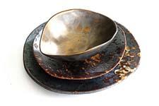 Special processing and time in the kiln create this unusual burnished gold, microwave-safe ceramic dinnerware. vancekitira.com