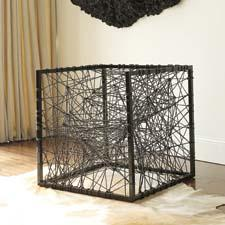 The striking Entropy chair from Phillips is a metal cubic structure containing a web of black cord, creating a one-of-a-kind place to sit. phillipscollection.com