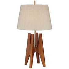 The Quatro table lamp from Pacific Coast Lighting is a mid-century item that features a dark fruitwood finish, a linen round shade, and the letter H in its design. pacificcoastlighting.com