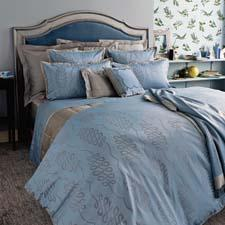 Calligraphie is a bed ensemble in an elegant pattern of loops, colored in blue and gray. yvesdelorme.com