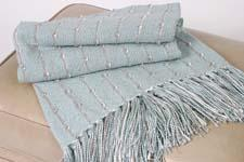 The Bamboo Ribbon throw, a handwoven mix of bamboo and cotton, now comes in a light sage color. textillery.com