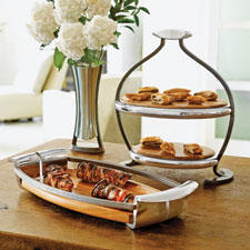 Nambé's aerodynamic Anvil Tray juxtaposes earthy wood and industrial-chic in a sleek, modern design. nambe.com