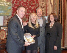 Wendy Fried of G. Fried Carpet & Design Center—left, and with her buyer and designer Iris Mendez, right—won Oriental Weavers' Options Rug Gallery contest for its displays highlighting Oriental Weavers' Options reversible area rug line. Brett Finkelstein, left, and Mike Riley, both of Oriental Weavers, presented Fried with an iPad for her winning entry last month.