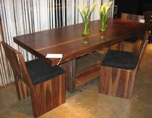 The Oliver dining table is part of the bina collection by Four Hands. The table and chairs are made with walnut solids.