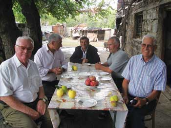Gary Hughes, left, enjoys lunch with a group of locals in rural Armenia.