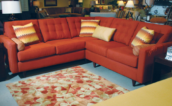 Klaussner Home Furnishings completed its showroom settings, like this one featuring the Craven sectional, with rugs from Surya.