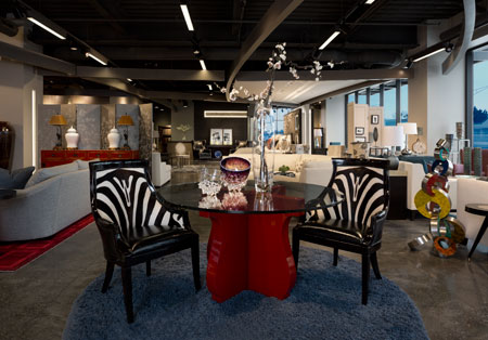 Maitland-Smith faux zebra hide dining chairs are paired with a Curate red piano lacquer base glass-top dining table and a Momeni Comfort Shag rug in peacock blue.