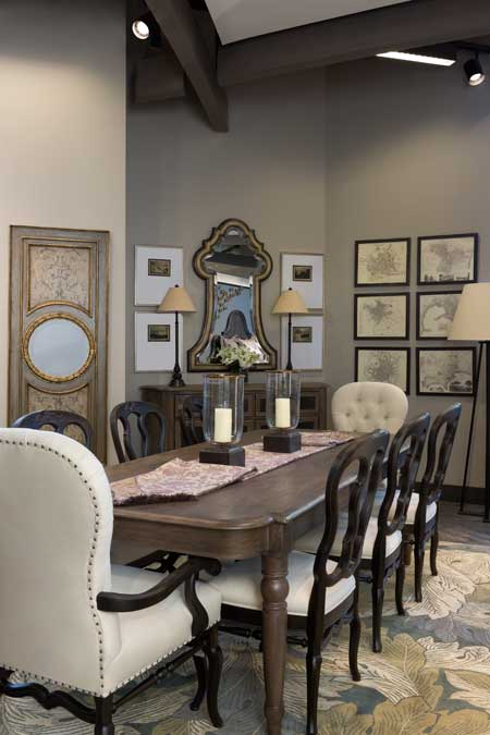 A Bernhard Belgian Oak dining room table, chairs and buffet, along with a John Richard leathered keyhole mirror, make a transitional statement at Scott Shuptrine Interiors in Royal Oak, Mich.