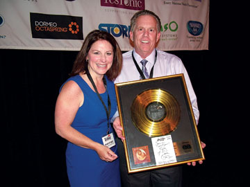Kristi Griggs, left, of G-Force Marketing, is presented with a Waylon Jennings gold record plaque after winning a raffle staged by Roger Magowitz, right, of the Seena Magowitz Foundation.