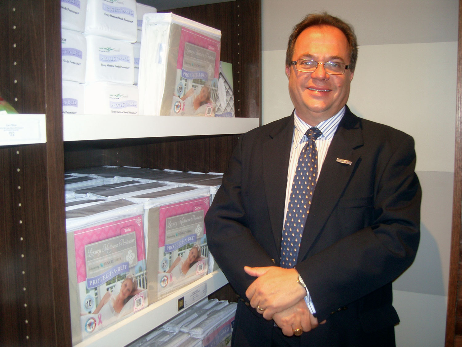 James Bell of Protect-A-Bed stands with a display of his company's mattress protectors at the store.