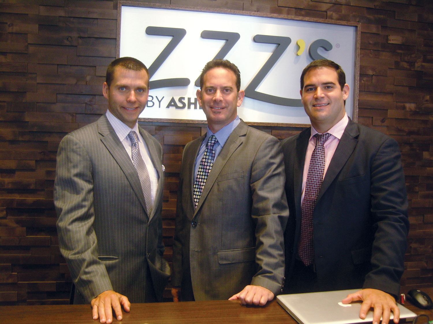 ZZZ's by Ashley executives Ben Thorud, left, Graeme Gordon and Andrew Disa stand inside the entrance to the new ZZZ's store.