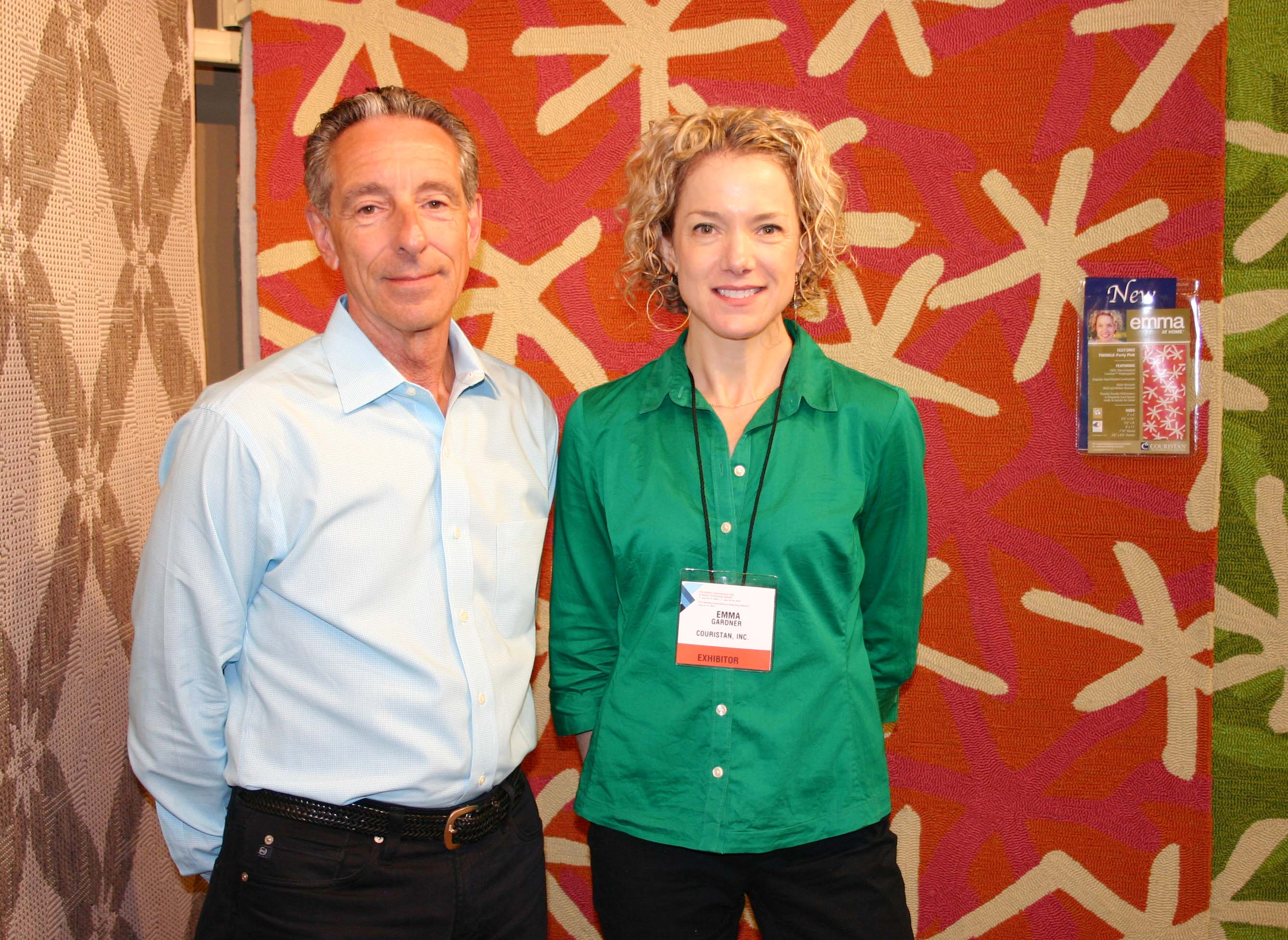 Steve Codella, Couristan executive vice president of sales (left) stands with Emma Gardner in front of Twinkle Party Pink, a hand-hooked, indoor/outdoor rug from Couristan's Emma at Home collection.