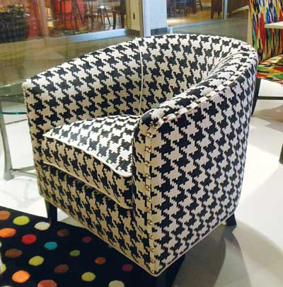 "Norwalk Furniture's barrel-back Sally chair in Keltic Oreo combines a simple, classic frame and tapered wood legs with ""exploding houndstooth"" fabric, according to company representatives. Large silver nail head trim adds edge to the profile."
