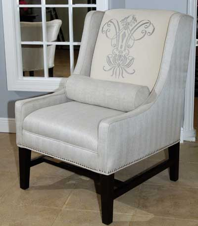 An accent roll pillow and crest add interest to this accent chair introduction by Aria Designs.