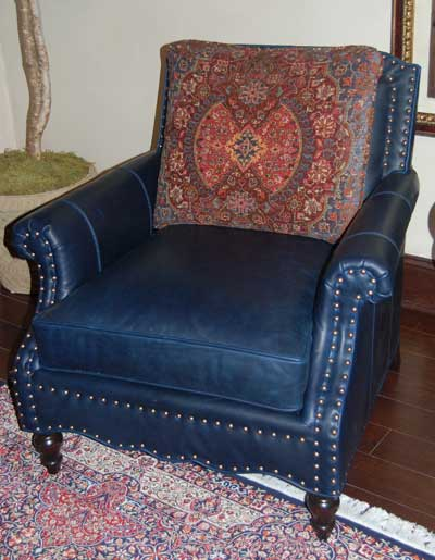 Lexington Home Brands pairs deep blue leather, nail head trim and vibrant multicolored fabric on the inner back to create the Belgrave chair.