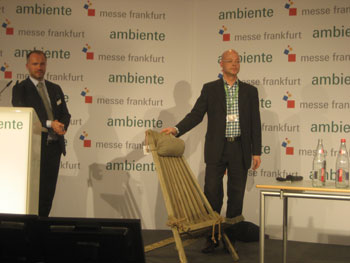 "Esa Salokorpi (right) of Finnish company EcoFurn Suomi demonstrates one of the company's chairs during a ""Speed Dating"" presentation, in which manufacturers each had five minutes to present a product. This chair is made entirely of wood, even held together without screws or nails."