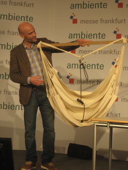 "Cornelius Grisar of La Siesta demonstrates one of the company's hanging chairs during a ""Speed Dating"" presentation. Made in Colombia, the chair features washable organic cotton fabric and a support bar made from FSC-certified wood."