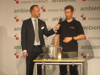 "Erdmann Kilian, director of marketing communications for Ambiente, interviews Harri Paakkanen, industrial designer for Lotus Grill, during the ""Speed Dating"" presentations. This stainless steel charcoal grill is smokeless thanks to a battery-powered fan."