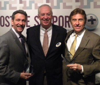 Receiving 2013 performance awards from Englander CEO and President Kevin Toman, center, during the Las Vegas Market were Dominic Azevedo, left, of Englander Southeast and Ed Ciolkosz of Englander Midwest.