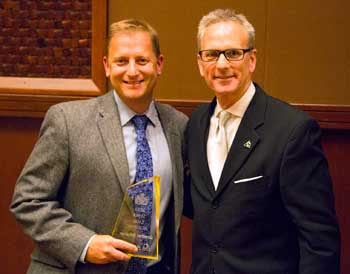 David Koehler, vice president of sales for AICO (right) presents Jonathan Schulman with the company's Professional of the Year award during AICO/Amini InnovatioN Corp.'s annual banquet in Las Vegas last month.