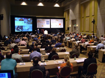A packed room of attendees enjoy speakers and panel discussions, addressing a wide variety of topics.