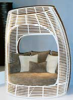 Designer Kenneth Cobonpue creates a private tete-a-tete seating with an oval rattan-enclosed frame.