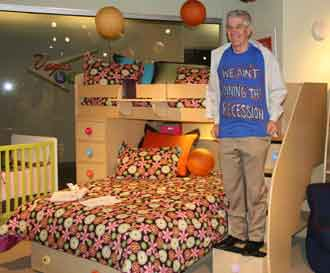 "Gallery Furniture's Jim McIngvale shows off his ""We ain't joining the recession"" T-shirt in the Berg Furniture showroom at the World Market Center in Las Vegas. He is standing on a step of Berg's twin-over-full Spacesaver group, a bestseller for both Houston-based Gallery and Berg."